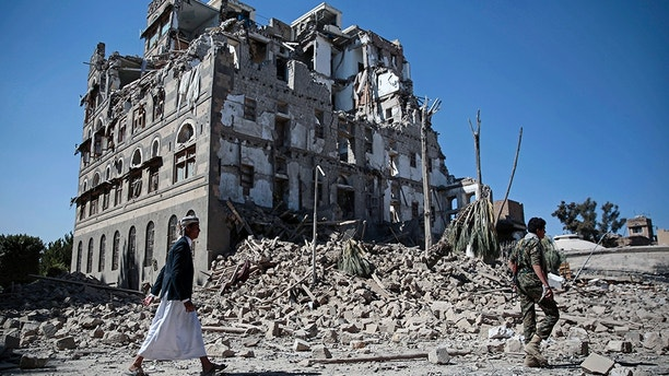 Houthi Shiite rebels walk amid the rubble of the Republican Palace that was destroyed by Saudi-led airstrikes, in Sanaa, Yemen, Wednesday, Dec. 6, 2017. (AP Photo/Hani Mohammed)