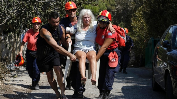 Members of a rescue team carry an injured woman in Mati, east of Athens, Wednesday, July 25, 2018. Rescue crews were searching Wednesday through charred homes and cars for those still missing after the deadliest wildfires to hit Greece in decades decimated seaside areas near Athens, killing at least 79 people and sending thousands fleeing. (AP Photo/Thanassis Stavrakis)