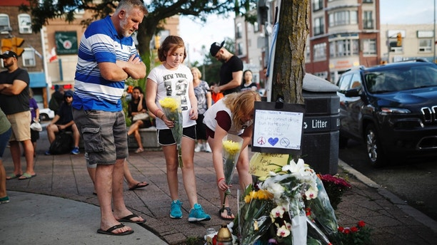 People add flowers and messages to a memorial remembering the victims of Sunday's shooting in Toronto on Monday, July 23, 2018. A man whose family said he suffered from psychosis and depression fired a handgun into restaurants and cafes in a lively Toronto neighborhood, killing a 10-year-old girl and an 18-year-old woman and wounding over a dozen others in an attack that has shaken the confidence of many in the normally safe city. (Mark Blinch/The Canadian Press via AP)