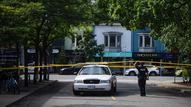 Police are shown at the perimeter of the scene of a shooting in east Toronto, on Monday, July 23, 2018. Police were trying Monday to determine what prompted a 29-year-old man to go on a shooting rampage in a popular Toronto neighborhood. (Christopher Katsarov/The Canadian Press via AP)