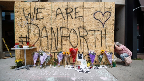 A woman writes a message on a makeshift memorial, Tuesday, July 24, 2018, in Toronto, for the victims of Sunday's shooting. Canadian investigators said Tuesday there was no link to terrorism in the mass shooting that killed two people and wounded 13 as they continued to probe the life of the 29-year-old gunman for clues to what prompted the rampage that targeted diners at restaurants and cafes in a popular Toronto neighborhood. (Mark Blinch/The Canadian Press via AP)