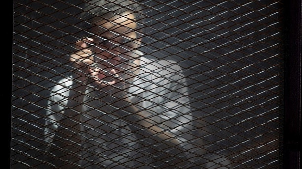 Egyptian photojournalist Mahmoud Abu Zied, known by his nickname Shawkan, gestures in a soundproof glass cage inside a makeshift courtroom in Tora prison in Cairo, Egypt, Saturday, July 28, 2018. Shawkan was arrested in August 2013 while taking photographs of the government's violent dispersal of a sit-in by supporters of ousted Islamist President Mohammed Morsi. (AP Photo/Amr Nabil)