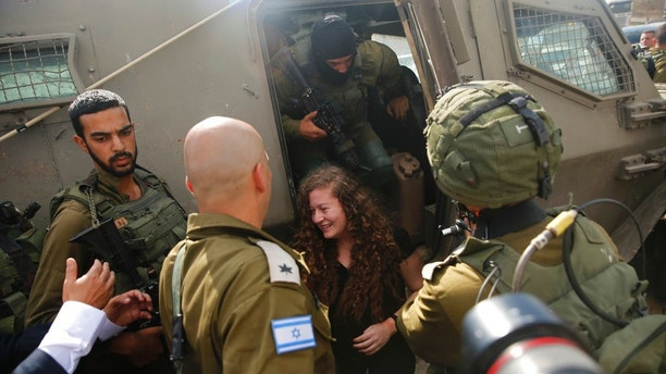Ahed Tamimi exits an armored military vehicle as she is released by the Israeli8 army Israeli prison after serving an eight month sentence at the entrance of her village of Nebi Saleh in the West Bank Sunday, July 29, 2018. (AP Photo/Nasser Shiyoukhi)