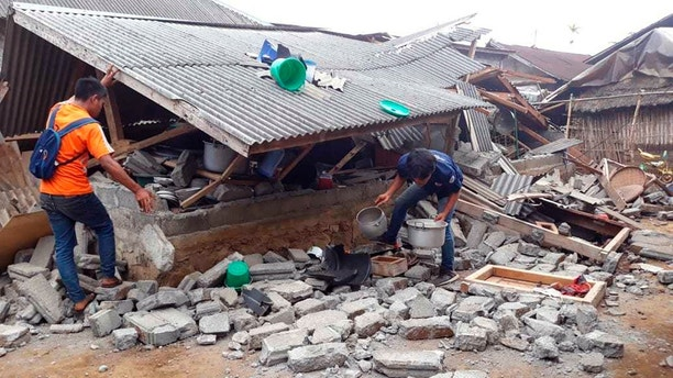 Villagers clear debris caused by an earthquake at Sajang village, Sembalun, East Lombok, Indonesia, Monday, July 30, 2018. A strong and shallow earthquake early Sunday killed more than a dozen people on Indonesia's Lombok island, a popular tourist destination next to Bali, officials said. (AP Photo)