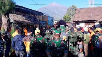 Indonesian soldiers and rescue team gather to prepare for evacuating tourists from Mount Rinjani, seen in the background, at Sembalun in East Lombok, Indonesia, Monday, July 30, 2018. A strong and shallow earthquake early Sunday killed more than a dozen people on Indonesia's Lombok island, a popular tourist destination next to Bali, officials said. (AP Photo)