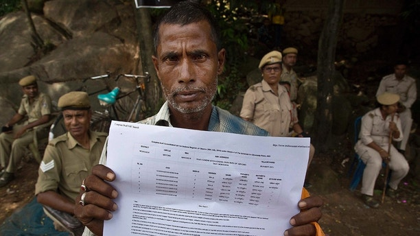 Muhammed Mainuddin, shows his name on a sheet collected from the National Register of Citizens draft center in Mayoung, about 55 kilometers (34 miles) east of Gauhati, India, Monday, July 30, 2018. India on Monday released a final draft of a list of its citizens in the northeastern state of Assam, leaving some 4 million people on edge to prove their Indian nationality. (AP Photo/Anupam Nath)