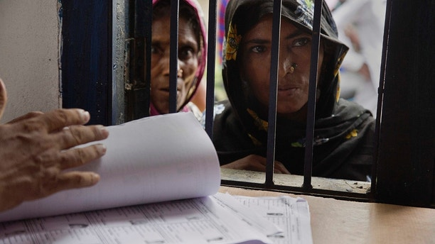 Muslim women stand in a queue to check if their names are included in the National Register of Citizens at a draft center in Mayoung, about 55 kilometers (34 miles) east of Gauhati, India, Monday, July 30, 2018. India on Monday released a final draft of a list of its citizens in the northeastern state of Assam, leaving some 4 million people on edge to prove their Indian nationality. (AP Photo/Anupam Nath)