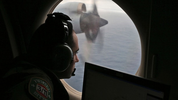 FILE - In this March 22, 2014, file photo, flight officer Rayan Gharazeddine scans the water in the southern Indian Ocean off Australia from a Royal Australian Air Force AP-3C Orion during a search for the missing Malaysia Airlines Flight MH370. An independent investigation report released Monday, July 30, 2018,  more than four years after Malaysia Airlines Flight 370 disappeared highlighted shortcomings in the government response that exacerbated the mystery. (AP Photo/Rob Griffith, File)