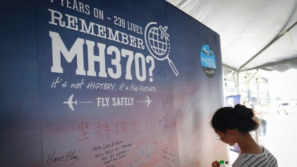 FILE - In this March 3, 2018, file photo, a girl writes a condolence message during the Day of Remembrance for MH370 event in Kuala Lumpur, Malaysia. An independent investigation report released Monday, July 30, 2018, more than four years after Malaysia Airlines Flight 370 disappeared highlighted shortcomings in the government response that exacerbated the mystery.(AP Photo/Vincent Thian, File)