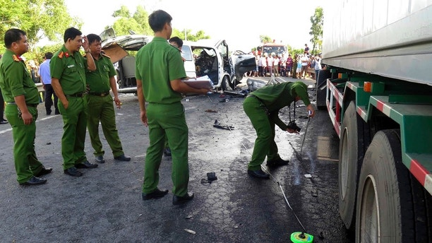 Police examine the scene after a wedding van collided into a container truck in Quang Nam province, Vietnam Monday, July 30, 2018. A van carrying a wedding party has crashed in central Vietnam, killing 13 people, including the groom.(Do Van Truong/Vietnam News Agency via AP)