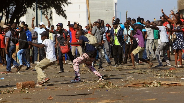 Opposition party supporters react after police fired tear gas, in Harare, Zimbabwe, Wednesday, Aug, 1, 2018. Hundreds of angry opposition supporters outside Zimbabwe's electoral commission were met by riot police firing tear gas on Wednesday as the country awaited the results of Monday's presidential election, the first after the fall of longtime leader Robert Mugabe. (AP Photo/Tsvangirayi Mukwazhi)