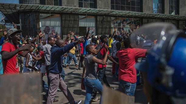 Opposition supporters gesture outside the Zimbabwe Electoral Commission offices in Harare, Zimbabwe, Wednesday, Aug. 1, 2018. Angry opposition supporters gathered outside Zimbabwe's electoral commission and were met by riot police on Wednesday as the country awaited the results of Monday's presidential election, the first after the fall of longtime leader Robert Mugabe. (AP Photo/Mujahid Safodien)
