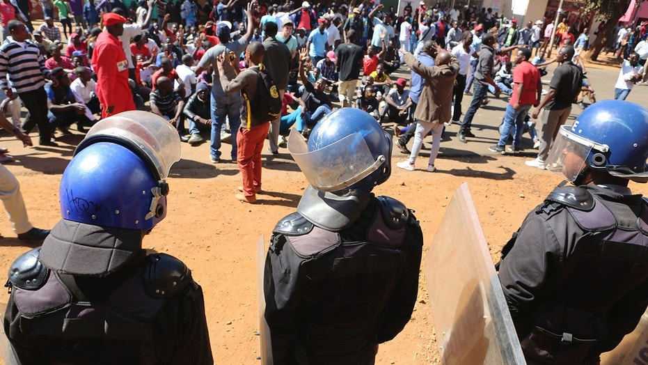 Police block dozens of opposition party supporters from entering the Zimbabwe Electoral Commission offices in Harare, Zimbabwe, Wednesday, Aug. 1, 2018. Zimbabwe's ruling party has won a majority of seats in Parliament, the electoral commission announced Wednesday, as the country braced for the first official results of the presidential election. (AP Photo/Tsvangirayi Mukwazhi)