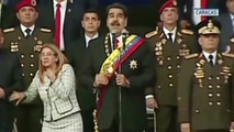 VIDEO STILL, BEST QUALITY AVAILABLE - In this still from a video provided by Venezolana de Television, Presiden Nicolas Maduro, center, delivers his speech as his wife Cilia Flores winces and looks up after being startled by and explosion, in Caracas, Venezuela, Saturday, Aug. 4, 2018. Venezuela's government says several explosions heard at a military event were an attempted attack on President Maduro. Information Minister Jorge Rodriguez said in a live broadcast that several drone-like devices with explosives detonated near the president. He said Maduro is safe and unharmed but that seven people were injured. (Venezolana de Television via AP)