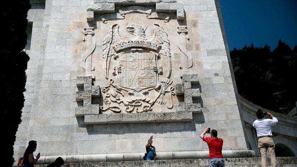 In this photo taken on Friday, July 13, 2018, a woman makes the fascist salute as she has her picture taken in front of the eagle escutcheon of the former Spanish dictator Francisco Franco regime at the Valley of the Fallen monument near El Escorial, outside Madrid. Spain's new government says that removing late dictator Gen. Francisco Franco from a glorifying mausoleum will be the first among many symbolic moves to come to terms with the country's troubled 20th century history. (AP Photo/Andrea Comas)