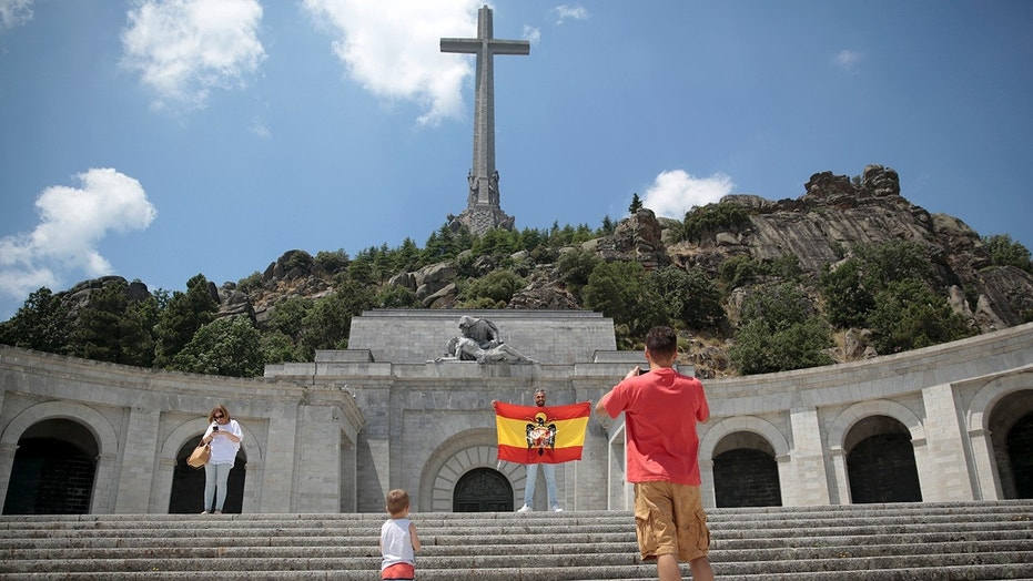 A man poses with a pre-constitutional Spanish flag of the former Spanish dictator Francisco Franco era at the Valley of the Fallen monument near El Escorial, outside Madrid, July 13, 2018.