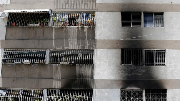 Signs of smoke cover the apartment complex where an allegedly armed drone crashed, causing a fire, in Caracas, Venezuela, Sunday, Aug. 5, 2018. Venezuelan President Nicolas Maduro dodged an apparent assassination attempt the previous day when drones armed with explosives detonated while he was delivering a speech to hundreds of soldiers being broadcast live on television, according to officials. (AP Photo/Ariana Cubillos)