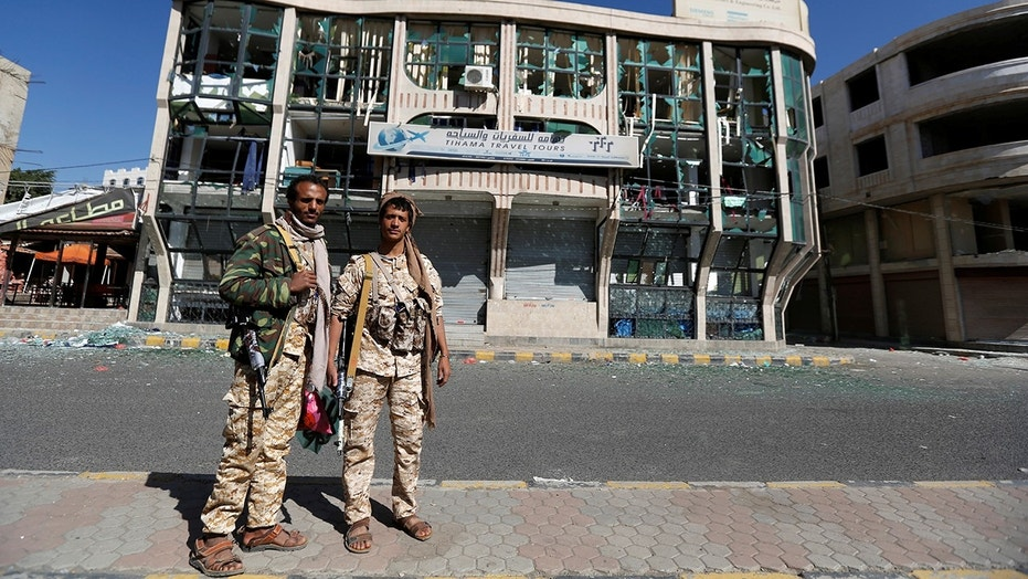 Houthi fighters pose for a photo in front of a damaged building on a street where Houthis have recently clashed with forces loyal to slain Yemeni former president Ali Abdullah Saleh in Sanaa, Yemen December 6, 2017. REUTERS/Khaled Abdullah - RC1A7A92EC80