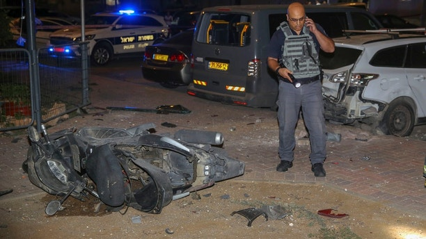 Israeli security stands at the site where a missile from Gaza Strip hit in the town of Sderot, Wednesday, Aug. 7, 2018. Sirens wailed in southern Israel warning of incoming projectiles from Gaza and Israeli media reported two people were lightly injured from shrapnel in the border town of Sderot. (AP photo/Yehuda Peretz)