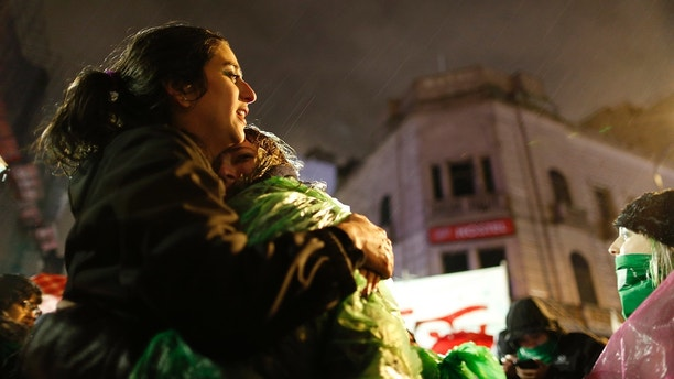 Tamara Deisel is embraced by her friend Florencia Buena as they stand under the rain outside Congress to show support for decriminalizing abortion as lawmakers debate the issue in Buenos Aires, Argentina, late Wednesday, Aug. 8, 2018. The Senate is debating a bill Wednesday that would legalize elective abortion in the first 14 weeks of pregnancy in the homeland of Pope Francis, setting up a vote that could reverberate around the region. (AP Photo/Natacha Pisarenko)