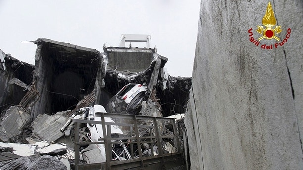 This photo released by the Italian firefighters, cars are seen among the rubble of the collapsed Morandi highway bridge in Genoa, northern Italy, Tuesday, Aug. 14, 2018. A large section of the bridge collapsed over an industrial area in the Italian city of Genova during a sudden and violent storm, leaving vehicles crushed in rubble below. (Vigili Del Fuoco via AP)