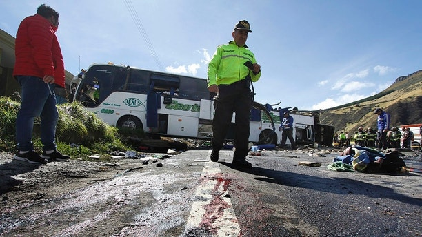A police officer walks past a Colombian-registered bus traveling to Quito that crashed in Pifo, Ecuador, Tuesday, Aug. 14, 2018. At least 24 people were killed and another 19 injured when a bus careened into another vehicle at high speed and overturned along the Pifo-Papallacta highway, near Ecuador's capital, local officials reported. (AP Photo/Carlos Noriega)