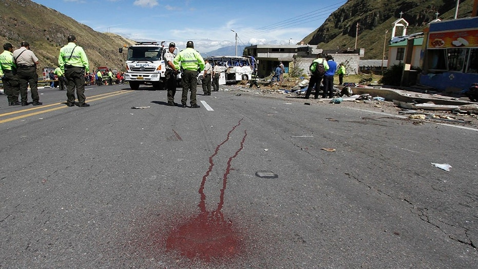 Police officers block traffic at the site where a Colombian-registered bus traveling to Quito crashed in Pifo, Ecuador.