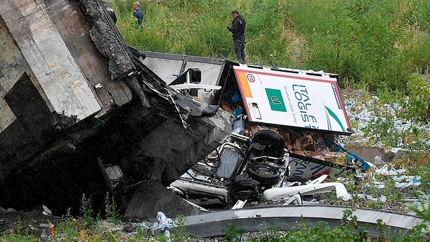 Rescues work among the debris of the collapsed Morandi highway bridge in Genoa, Tuesday, Aug. 14, 2018. Italian authorities say that about 10 vehicles were involved when the raised highway collapsed during a sudden and violent storm in the northern port city of Genoa, while private broadcaster Sky TG24 said the collapsed section was about 200-meter long (650 feet). (Luca Zennaro/ANSA via AP)