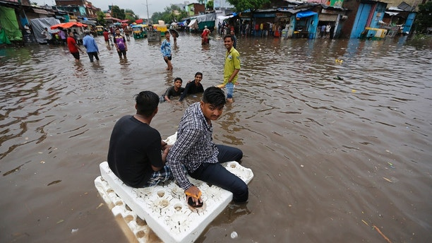 Indian men use thermocol sheets as a makeshift raft on a flooded road after heavy rainfall in Ahmadabad, India, Friday, Aug. 17, 2018. India receives its annual rainfall from June-October. (AP Photo/Ajit Solanki)