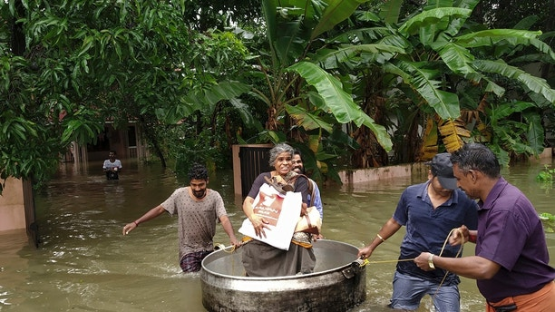 An elderly woman is rescued in a cooking utensil after her home was flooded in Thrissur, Kerala state, India, Thursday, Aug.16, 2018. Torrential monsoon rains have disrupted air and train services in the southern Indian state of Kerala, where flooding, landslides and bridge collapses have killed dozens of people in the past week, officials said. (AP Photo/K.K.Najeeb)