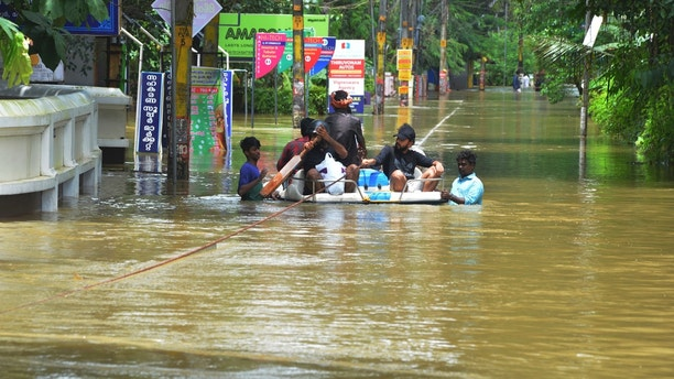 People move past a flooded area in Thrissur, in the southern Indian state of Kerala, Friday, Aug. 17, 2018. Rescuers used helicopters and boats on Friday to evacuate thousands of people stranded on their rooftops following unprecedented flooding in the southern Indian state of Kerala that left more than 100 dead. (AP Photo)