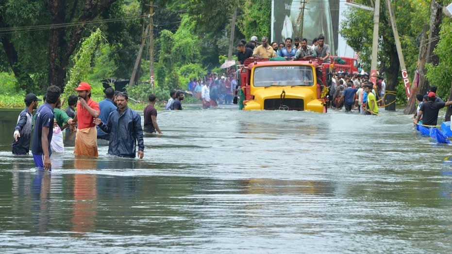 A truck carries people past a flooded road in Thrissur, in the southern Indian state of Kerala, Saturday, Aug. 18, 2018.