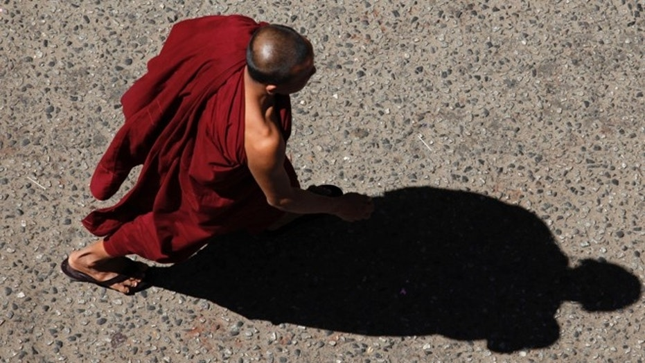 """A Buddhist monk was charged after he allegedly beat a young boy for """"playful"""" behavior during a prayer ceremony."""