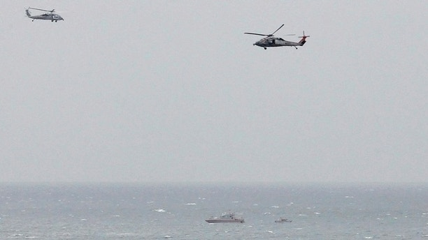 FILE PHOTO: A Iranian Revolutionary Guard boat is seen near the U.S. aircraft carrier, USS George H. W. Bush while transiting Straits of Hormuz as U.S. Navy helicopters hover over it during early hours of March 21, 2017. REUTERS/Hamad I Mohammed/File Photo - RC1C32AA2400