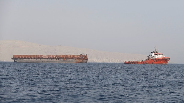 FILE PHOTO: A tug boat moves cargo towards the Strait of Hormuz, in Musandam province, Oman, July 20, 2018. Picture taken on July 20, 2018. REUTERS/Hamad I Mohammed/File Photo - RC1549765850