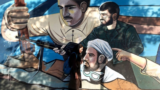 An Iranian woman walks past a mural depicting members of Basij paramilitary force, portraying Iranians' solidarity against their enemies, painted on the wall of a government building at the Felestin (Palestine) Sq. in downtown Tehran, Iran, Monday, July 30, 2018. Iran's currency has dropped to a record low ahead of the imposition of renewed American sanctions, with many fearing prolonged economic suffering or possible civil unrest. (AP Photo/Ebrahim Noroozi)