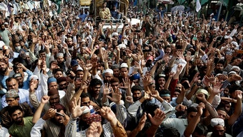 Supporters of Pakistani religious group shout slogans during a march towards Islamabad Wednesday, Aug. 29, 2018 in Lahore, Pakistan. Thousands of Islamists in Pakistan launched a march toward the capital on Wednesday to protest a far-right Dutch lawmaker's plans to hold a Prophet Muhammad cartoon contest later this year. (AP Photo/K.M. Chaudary)