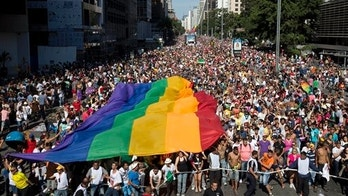 Participants carry a rainbow flag as thousands march during the annual Gay Pride Parade in Sao Paulo, Brazil, Sunday, May 4, 2014. Gay rights advocates are calling for a Brazilian law against discrimination as they gather by the hundreds of thousands in Sao Paulo for one of the world's largest gay pride parades. (AP Photo/Andre Penner)
