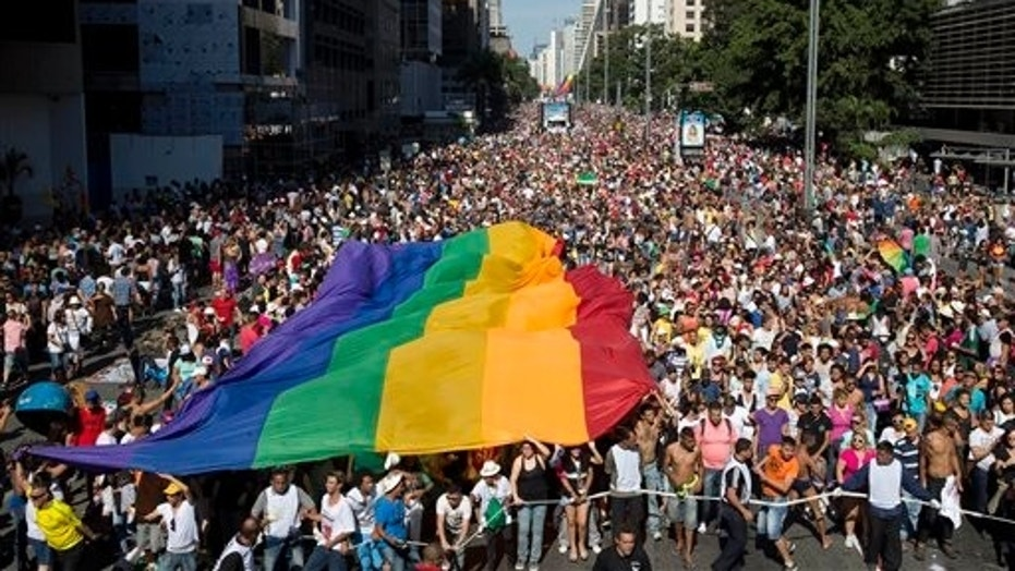 Participants carry a rainbow flag as thousands march during the annual Gay Pride Parade in Sao Paulo, Brazil, Sunday, May 4, 2014.
