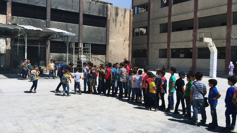 In this Wednesday, Sept 5, 2018 photo, Syrian students play in the courtyard of a school whose walls are still charred and pockmarked with bullets from recent fighting in the town of Douma, in the eastern Ghouta region, near the Syrian capital Damascus, Syria. Millions of Syrian children return to school as the country's conflict simmers down. The Syrian government is keen to project a sense of normalcy, opening hundreds of newly renovated schools and calling on students to wear uniforms, which were shed in years of chaos. But humanitarians say the war is far from over, particularly its scars on children. (AP Photo)