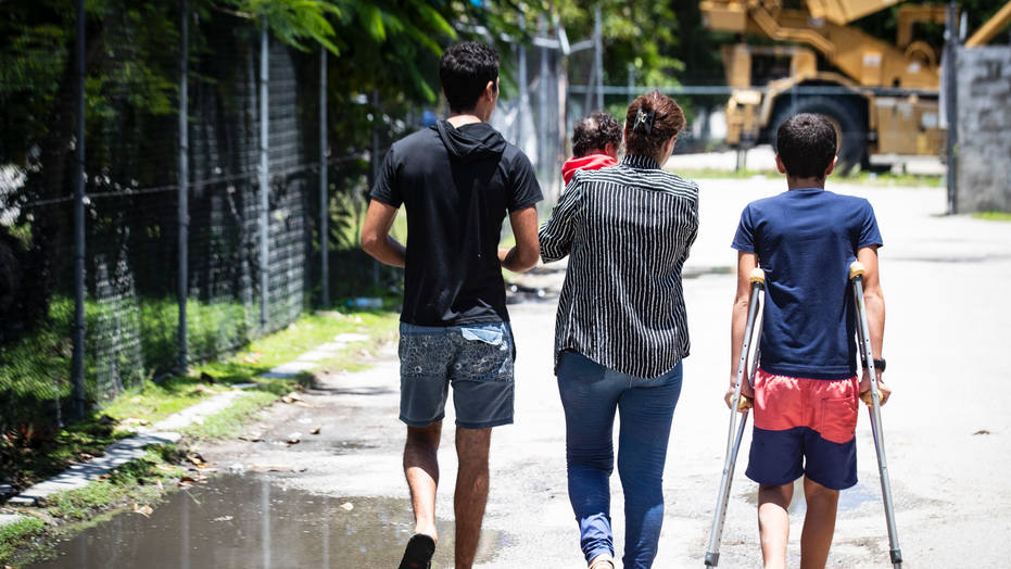 "In this Sept. 4, 2018, photo, from left, Mohammad, 17, Aryana, 2 1/2 months old, his mother and little brother Amirparsa, 11, are pictured on Nauru. ""We were innocent,"" says Mohammad about himself and other children. ""It was not our fault to come out of our countries. It was not our fault to be in Nauru. We need future. We need education. We need to be in a normal place."" (Jason Oxenham/Pool Photo via AP)"