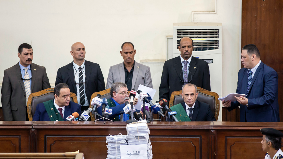 Judge Hassan Faried, center front, sits in the court in Cairo, Egypt, Saturday Sept. 8, 2018. In a case involving 739 defendants, the Egyptian court on Saturday sentenced 75 people to death, including top leaders of the outlawed Muslim Brotherhood, for their involvement in a 2013 sit-in protest. Mahmoud Abu Zaid, a photojournalist also known as Shawkan whose case was embraced by rights groups, received five years imprisonment, meaning he will walk free for time served. (AP Photo/Roger Anis)