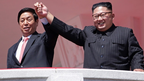 North Korean leader Kim Jong Un, right, raises hands with China's third highest ranking official, Li Zhanshu, during a parade for the 70th anniversary of North Korea's founding day in Pyongyang, North Korea, Sunday, Sept. 9, 2018. North Korea staged a major military parade, huge rallies and will revive its iconic mass games on Sunday to mark its 70th anniversary as a nation. (AP Photo/Kin Cheung)