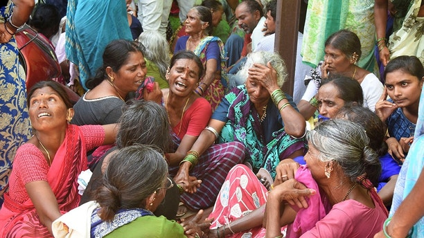 Relatives of victims of a bus accident wail near a hospital in Jagtiyal district of Telangana, India, Tuesday, Sept. 11, 2018. A bus carrying pilgrims from a Hindu temple in the hills of south India plunged off a road Tuesday, killing more than 50 people including four children, officials said. (AP Photo)