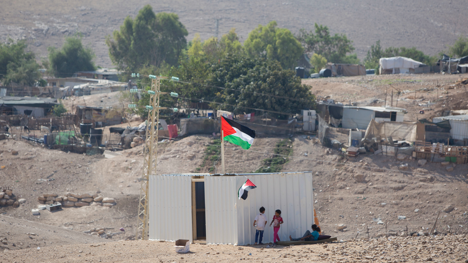 Palestinians girls sit by newly made shed in the West Bank Bedouin community of Khan al-Ahmar, Tuesday, Sept. 11, 2018. Israel says Khan al-Ahmar was illegally built and has offered to resettle residents 12 kilometers (7 miles) away. Critics say its removal is meant to make room for an Israeli settlement. Israel's Supreme Court rejected an appeal last week, paving the way for demolition. (AP Photo/Majdi Mohammed)