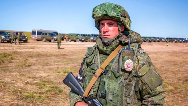 In this photo provided by Russian Defense Ministry Press Service on Tuesday, Sept. 11, 2018, a Russian soldier guards an area during the military exercises in the Chita region, Eastern Siberia, during the Vostok 2018 exercises in Russia. Russia's military chief of staff says that the military exercises expected to be the biggest in three decades, will involve nearly 300,000 troops. (Russian Defense Ministry Press Service pool photo via AP)