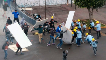 In this photo provided by the Andina government news agency, Alianza Lima club soccer fans, left, fight with members of an evangelical church, yellow helmets at right, outside the soccer club's stadium in Lima, Peru, Monday, Sept. 10, 2018. The two groups clashed outside the stadium over who has the right to use the area surrounding the sports venue, after the religious group arrived early in the morning and started removing the team's logos from the parking area. (Norman Cordova/Andina News Agency via AP)