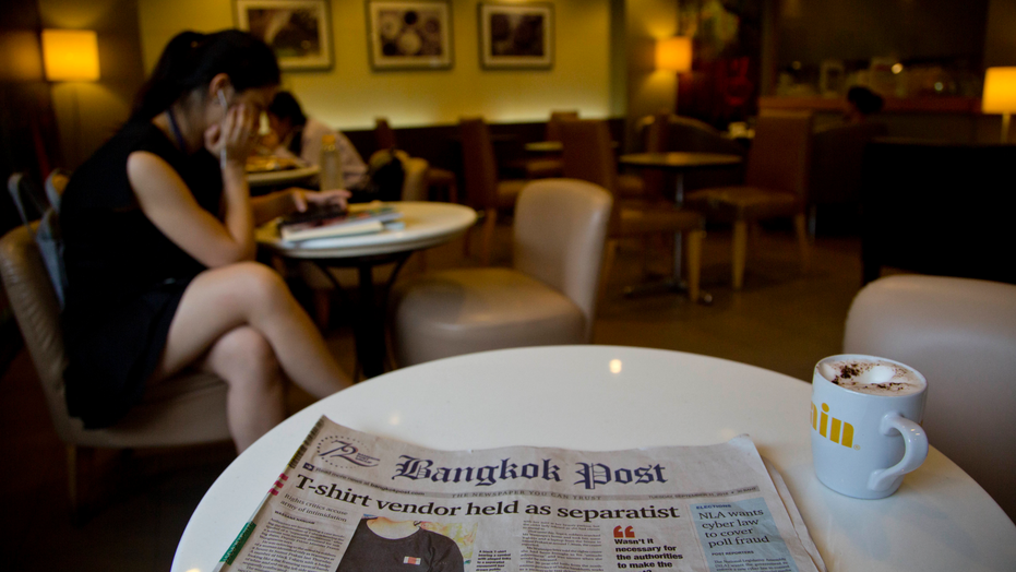 Thailand's Bangkok Post newspaper depicting a cover story on detention of a vender who sold black t-shirts, bearing a symbol allegedly linked to a movement promoting a federal republic, is placed on a table at a cafeteria in Bangkok, Thailand, Tuesday, Sept. 11, 2018. Thailand's military government this past week launched a crackdown on a small anti-government movement advocating a federal republic, arresting its alleged sympathizers on the basis of their owning t-shirts bearing the group's logo of a tiny red and white flag. (AP Photo/Gemunu Amarasinghe)