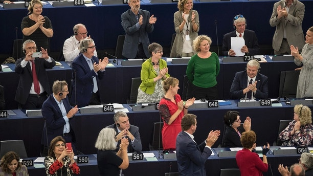 Members of the European Parliament applaud Dutch MEP Judith Sargentini, third right in green, second row from top, after members of the European Parliament after a vote in Strasbourg, eastern France, Wednesday, Sept.12, 2018. EU lawmakers have voted in favor of launching action against the Hungarian government of Prime Minister Viktor Orban for allegedly undermining the bloc's democratic values and rule of law. (AP Photo/Jean-Francois Badias)