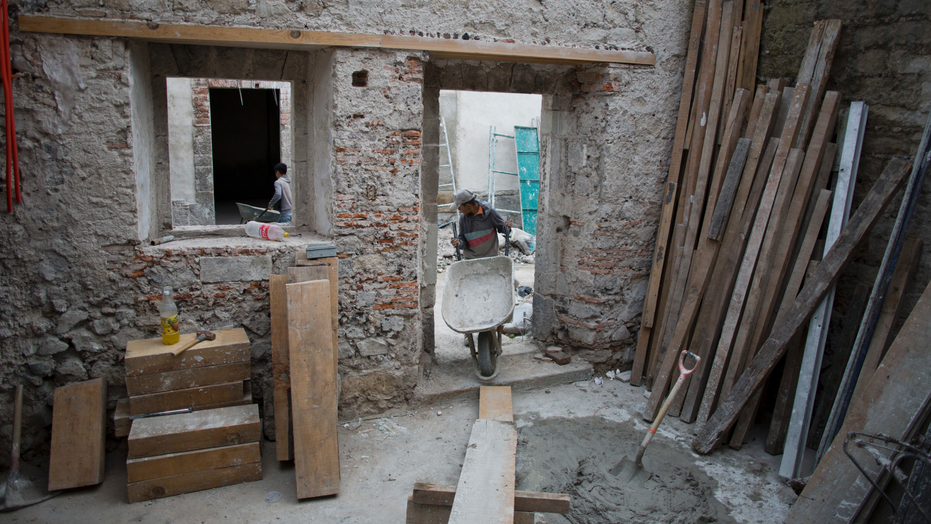In this Monday, Sept. 10, 2018 photo, a mason pulls a wheelbarrow inside the building of 25 Manzanares Street, in Mexico City. The nondescript building on Manzanares Street survived dozens of magnitude-7 earthquakes and repeated floods, including one following a 1629 rainstorm that lasted five years. (AP Photo/ Eduardo Verdugo)